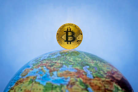 Bitcoin gold coin. Virtual cryptocurrency concept. Bitcoin as a symbol world currency. The cryptocurrency bitcoin on the globe. globalization, globalize, worldwide, universal, global, international,