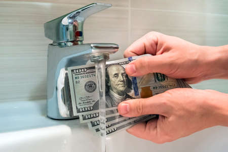 Cleaning a dirty American one hundred dollar bill. money on the black market. Banknotes of 100 dollars in the hands of men near water jets in washbasin.