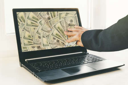 man or businessman holding buck money in his hand. Laptop in the background. electronic business. dollars on the screen. Earn money online with a computer. profit from trading on the stock exchange Stock fotó