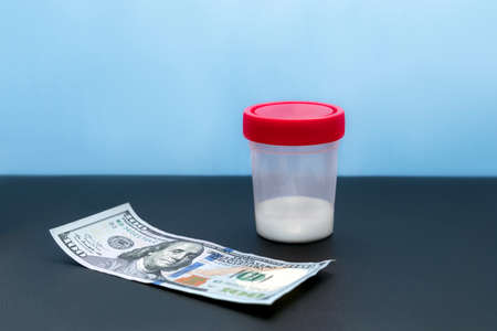 A plastic container with a small amount of sperm and dollars on a black table against a blue background. Spermbank. money for sperm donation. reproductive medicine. buying sperm spermbank. Stock Photo