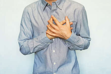 grown men with symptoms of acute recurrent heart attack. guy clinging heart on a blue background. chest pain. preinfarction angina, Heart failure, Angina, Tachycardia, Pericarditis,
