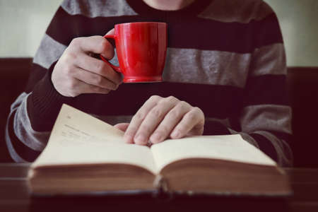 Business man reading book with coffee in coffee shop close-up. page turning Stock Photo