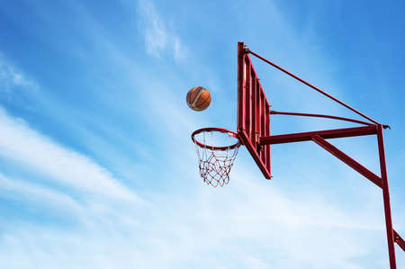 Old Basketball ring on blue sky background with ball into a basket.