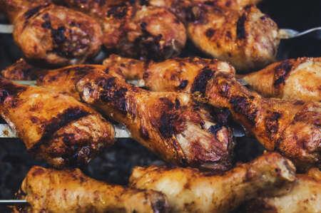 Pollo a la parrilla en un pincho con una deliciosa corteza frita crujiente. La vista desde la cima. Barbacoa de carbón de leña caliente llameante primer plano. Foto de archivo - 92507861