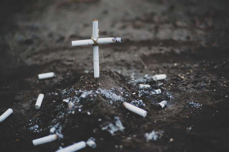 A cemetery with a grave made of cigarettes. Death by harm from nicotine or tobacco smoke from cigarettes. Cigarette kills.