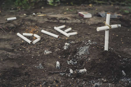 a cross from butts. Smoking kills. inscription die laid out the cigarettes on the ground next to the grave. the concept of anti-Smoking.