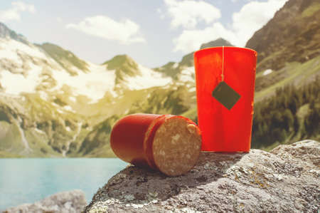 Orange plastic mug with strong tea and tea bag on a snowy winter background. Tourist knife cuts smoked sausage. Stock Photo