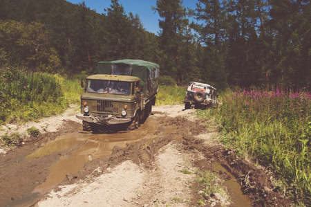Heavy powerful truck-terrain vehi cle with off-road wheels. Big off-road truck pulls pross small SUV. Pull the car stuck in the mud. Banque d'images