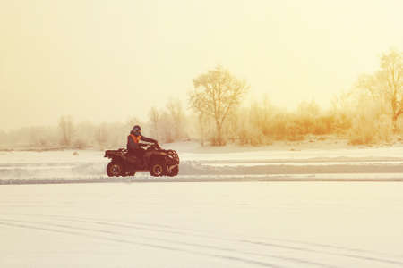 The ATV rider rides on the ice at sunset in winter, in winter the frozen lake. Winter riding on motorbikes. cold extreme. beautiful nature winter