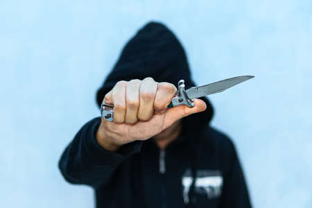 A young man in a hoodie holding a knife symbolizing youth crime. Crime concept. The threat of a cold weapon. A terrorist from ISIS with a knife. A prisoner with a Shiv. Stock Photo