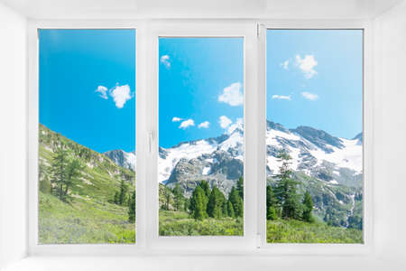 Landscape view through modern window in room. White plastic three-chambered three-sided box
