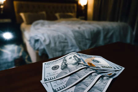 a large sum of us dollars on the table on a blurred bedroom background. selling love