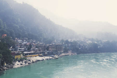 Holy Ganges river that flows through Rishikesh the world capital of Yoga - the holy city for the Hindus, India. Gloomy city in the fog. Beautiful scenery. The morning haze.