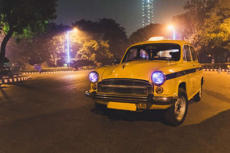 Yellow classic taxi service at Kolkata airport parking at night. A taxi model 50s-60s.