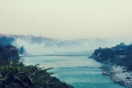 Amazing landscape of bridge of river, fog evaporate from pond make romantic scene or Beautiful bridge on lake with trees at fog. Iron bridge over river in misty morning. suspension bridge. Rishikesh Stock Photo