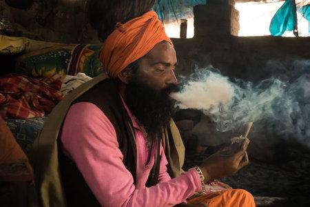 Goa, INDIA - January 11, 2018: A unidentified sadhu is smoking ganja marihuana. Babba the sacred teacher, guru and mentor smokes Smoking jamb with drugs.