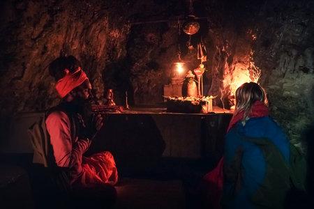 meditation lesson in an ancient sacred old cave near Rishikesh India. Sadhu, guru and spiritual guide conduct meditation sessions for pilgrims. January 11, 2018: Rishikesh India