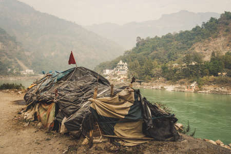Beggar's hut by the river Ganges Rishikesh on the background of a large expensive temple. lower caste. Social inequality. The problem of poverty and the caste system of India
