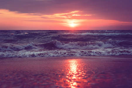 Un hermoso amanecer en la isla de Sanibel, Florida. Brillante intenso rosa púrpura naranja amanecer en el mar. Olas al amanecer. reflejo de la luz solar en agua y arena en la playa. Marea al amanecer. Vista dramática