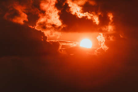 Summer background with a magnificent sun burst. Hot with space for your message. Bright red sun in the nes with clouds. The evening sunset. The sun is hiding behind the clouds Stock Photo