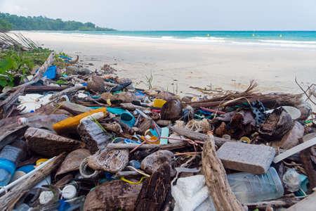 Zanieczyszczenia na plaży tropikalnego morza. Plastikowe śmieci, pianka, drewno i brudne odpady na plaży w letni dzień. Zdjęcie Seryjne