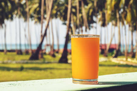 A glass of orange juice is placed on the table in the background of the palm grove. beautiful tropical island landscape. On the background of the palm grove.