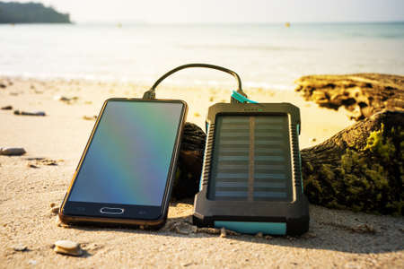 Battery solar energy device on a background of the sandy beach of an uninhabited island. Charge smart phone from the solar battery. 스톡 콘텐츠