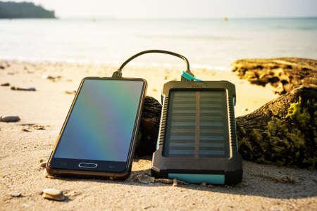 Dispositivo de energía solar de batería sobre un fondo de la playa de arena de una isla deshabitada. Cargue el teléfono inteligente con la batería solar.