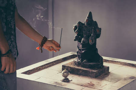a man brings a fragrant Smoking stick to the pagan totem.. Hindu god Ganesh on black background. Statue on wooden table with a smoke of incense. fragrant wand