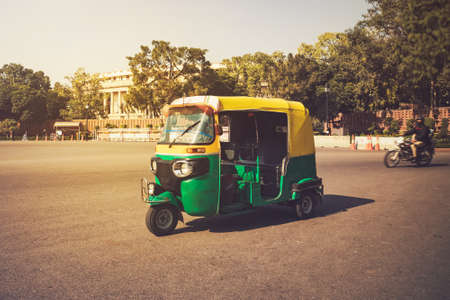 Moto-Rickshaw, New Delhi, India. Indian taxi stands on the street against the backdrop of the presidential Palace. Expensive area of the city. Stock Photo