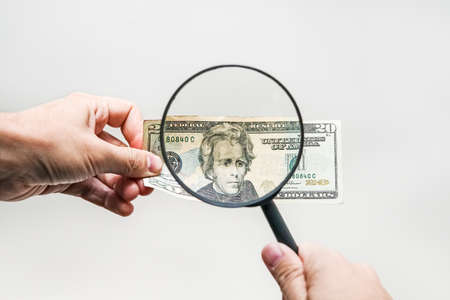 two dollar bill and magnifying glass isolated on white