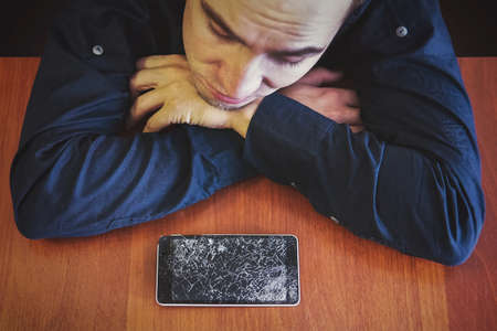 A man looks at his broken phone lying on a wooden table with a sad look. guy was upset about breaking his phone. Shattered phone display