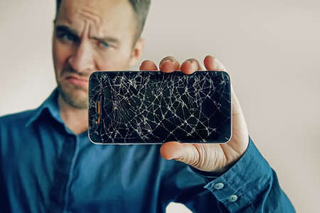 The guy is holding a black smartphone with a broken display. Broken screen of modern frameless phone. a large crack in the form of a web on the smartphone screen close-up. Stok Fotoğraf