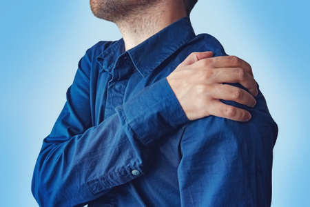 Businessman holding his hand to his aching back. A young guy in a blue shirt complains of pain in his shoulder. fracture of the forearm. concept of health