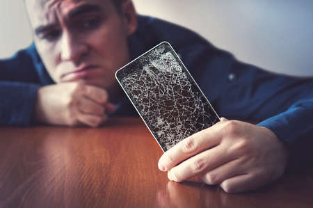 Hands holding a mobile phone with a broken screen over the wooden surface. A man looks at his broken phone lying on a wooden table with a sad look. guy was upset about breaking his phone.