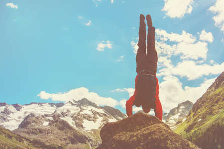 Practice gymnastic exercises in the open air in nature. Stuntman doing a dangerous trick on the edge of a precipice high in the mountains, handstand. Insanely dangerous stunts. tinted photo.