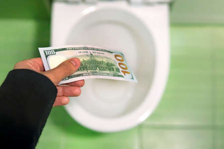 Flush money down the toilet, throws dollar bills in the toilet, loss concept, close up, selective focus.