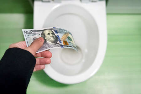 concept of senseless waste of money, loss, useless waste, large water costs, 100 Dollar bills flushed into a toilet bowl. loss of money, losing money