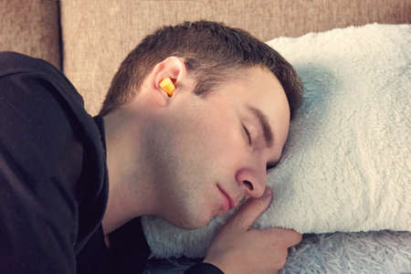 Young handsome guy is asleep on the couch wearing black t-shirt. Close up portrait. Day rest, Siesta. yellow ear plugs in the ears of men Banco de Imagens