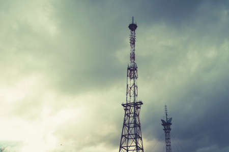 Radio telecommunications tower, Mobile phone tower and old steel pipe in storm clouds. dramatic landscape with cloud storm cloud and metal TV tower