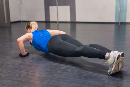 young fitness woman doing push ups. Athlete with white hair in the stand for push-UPS. Athlete in a blue shirt and black leggings involved in sports. Imagens