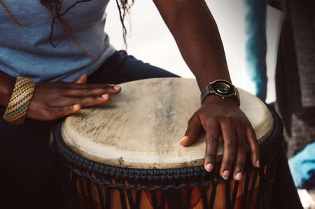 Close up of hands of a woman playing a drum. Nigerian woman playing a traditional African drum