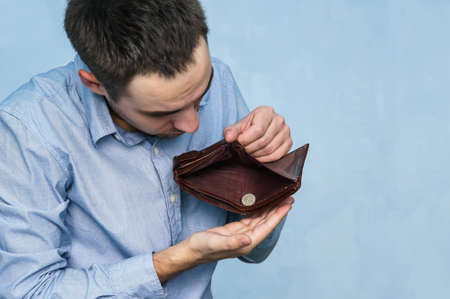 The guy pulls out the last ruble out of an empty purse. Poverty and unemployment. Man with no money. Businessman holding empty wallet. Stock Photo