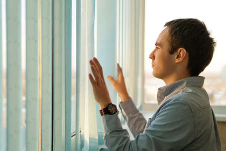 Pensive man thinking of something behind venetian blind. The young guy pushes the vertical blinds in front of window and looking into the distance. Businessman in office looking out window. Vertical 版權商用圖片