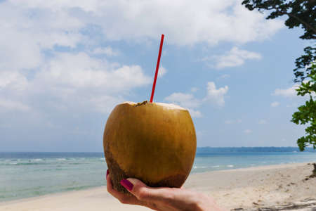 Fresh coconut cocktail in hand on turquoise sea background, travel card, with crooked horizon line. Drink coconut milk on the beach. southeast Asia. healthy fruit drink that quenches thirst well Stock Photo