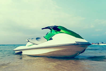 Jet ski moored in shallow water off a beach ready to be taken out to sea by holidaymakers and tourists 스톡 콘텐츠