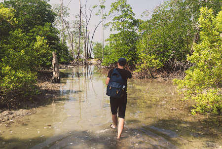 young man walks through the flood with his bare feet. tourist makes his way through the marshland surrounded by mangroves. tourist make their way through the swamp.