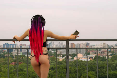Sexy girl with headphones looks at the city from above leaning on the railing. Informal non-standard appearance. Rear view. The woman with the African pigtails.