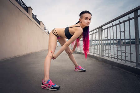 Close up portrait of beautiful woman with tattoo. Informal model posing on the background of the waterfront. Naked girl in black bra and sexy panties and pink sneakers. African braids in long hair