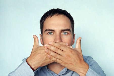 el hombre le cubre la boca. El empresario cierra la boca. Foto de archivo